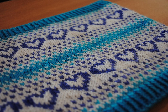 Close up of knitted cowl featuring color work hearts in shades of teal, purple, and white.