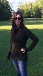 Light skinned brunette woman wearing sunglasses and a dark green hand knit pullover sweater and standing in an open grassy area in the bright sunlight.