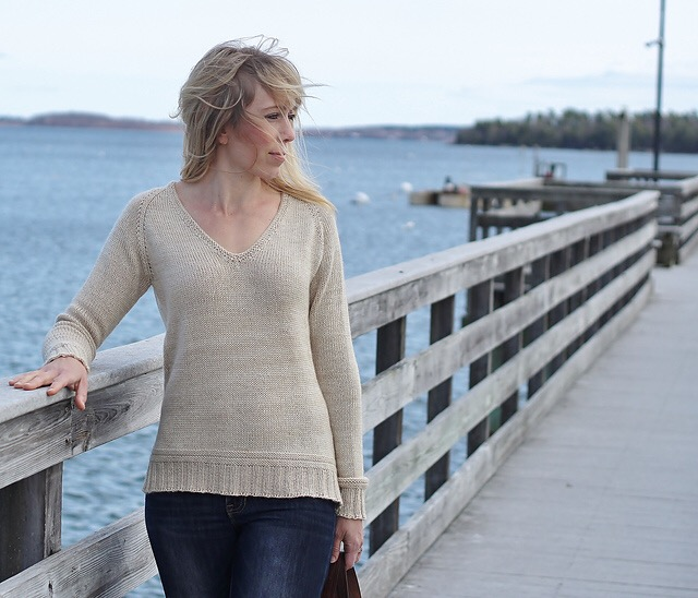 Blond light skinned woman wearing a hand knit ecru pullover while standing on a boat dock.