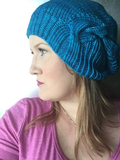 Woman wearing blue hand knit cabled hat.