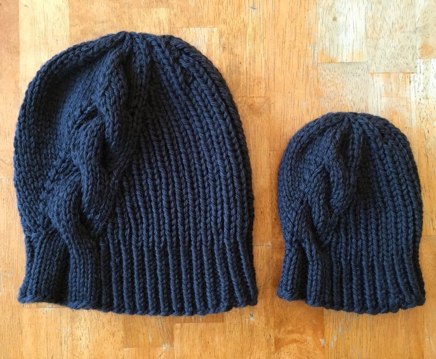 Two gray knit hats on a wooden table.