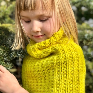 Girl wearing Camber Eclipse Cowl while standing among evergreen trees.