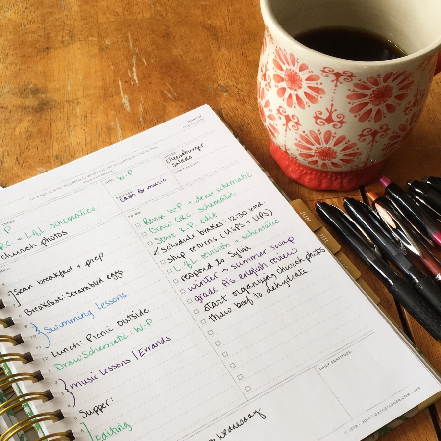 Coffee mug and daily planner with color-coded entries.