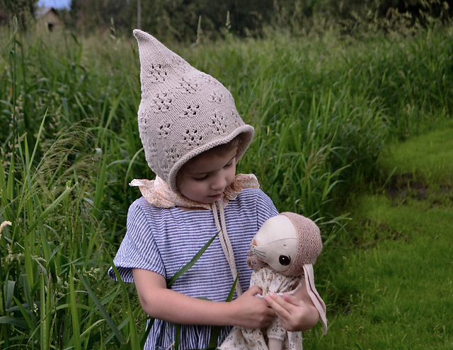 Young girl wearing hand-knit pixie bonnet and holding handmade bunny stuffed toy while standing in a field boarded by long grass.