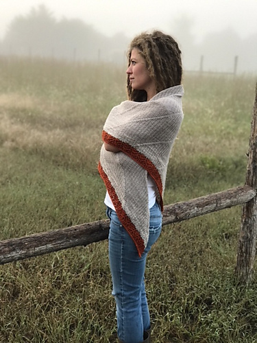 Woman wrapped in shawl and standing in a foggy field.