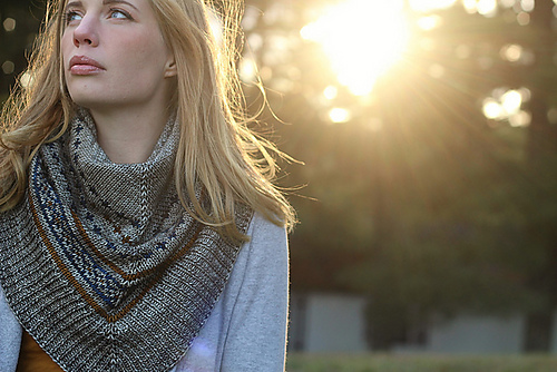 Woman wearing colorwork shawl with sun filtering through the trees.