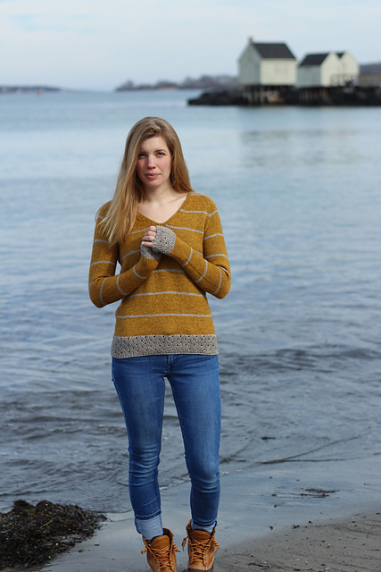 Woman wearing striped gold and silver sweater while standing on the shoreline.