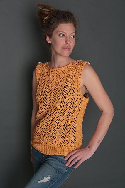 Woman wearing yellow sleeveless lace top.